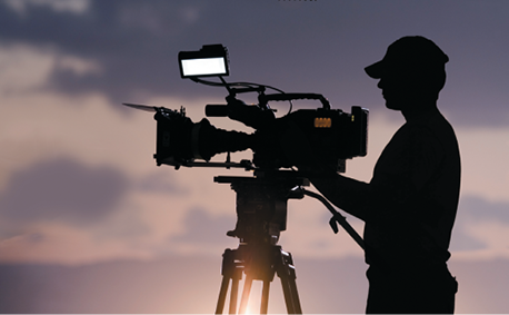 A television camera and camera man silhouetted against a sunset sky.