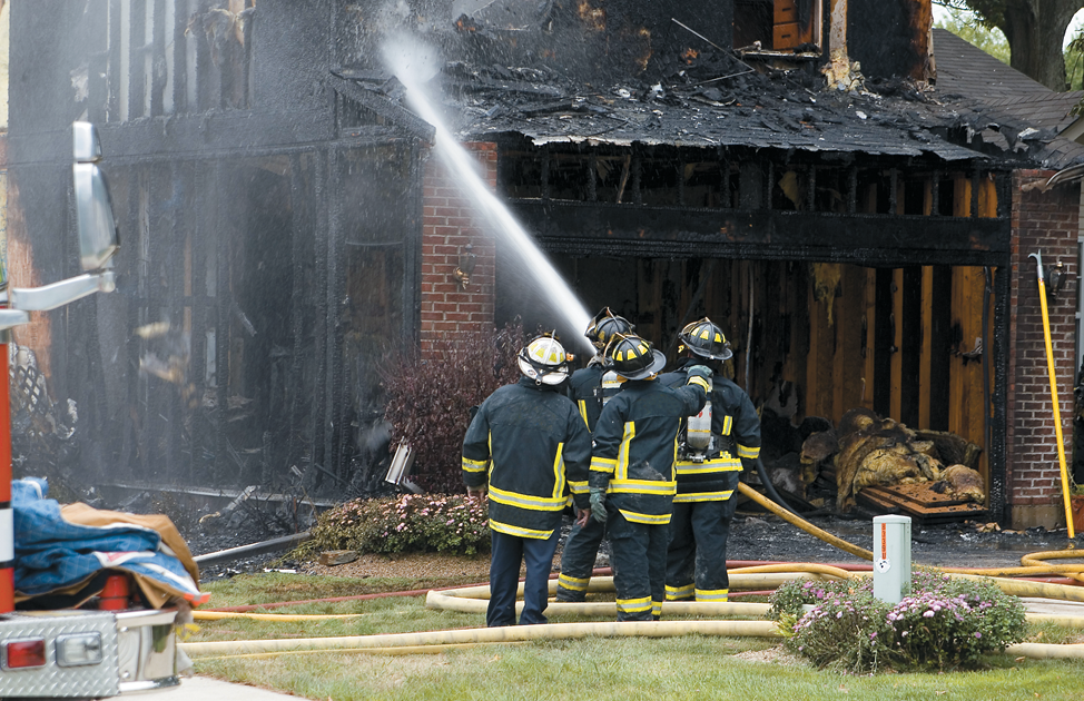 A team of four firemen are hosing the burnt shell of a house.
