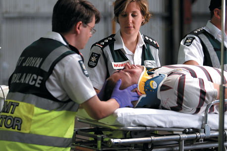 Three uniformed St John Ambulance staff are treating and transporting a male patient with a neck brace on a gurney.