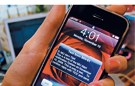 Close up of a woman's hand holding a smart phone displaying an emergency alert text message
