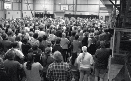 A large group of people standing in a gymnasium.