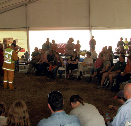 A couple dozen people are seated or standing in a marquee being addressed by an emergency services officer.