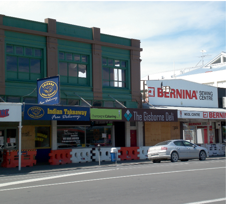 A row of street-front shops with boarded-up windows and safety barriers.