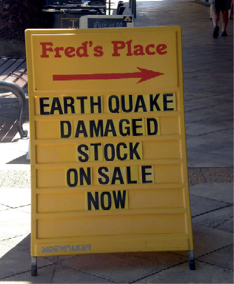 An A-frame sign on a footpath reads Fred's Place: Earthquake damaged stock on sale now.