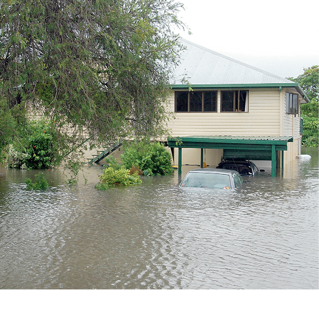 An elevated home is surrounded by floodwater such that the cars in the driveway are mostly submerged.
