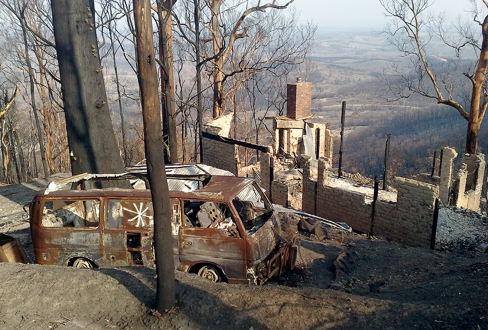 A post-fire scene showing a burnt-out house and van, and a blackened landscape.