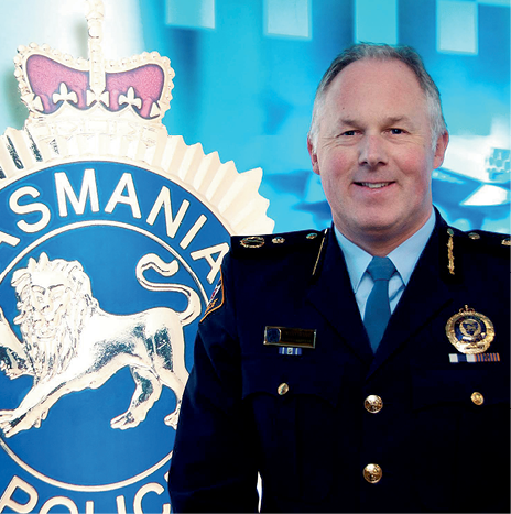 A photograph of Scott Tilyard, Tasmania's Deputy Commissioner of Police. He is wearing a dark blue uniform and standing in front of a large image of the Tasmanian Police logo, which has a lion and a crown on it.