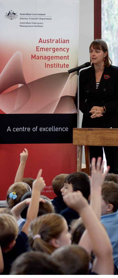 Photograph of the Hon Nicola Roxon speaking behind a podium in front of an audience of young children with raised hands