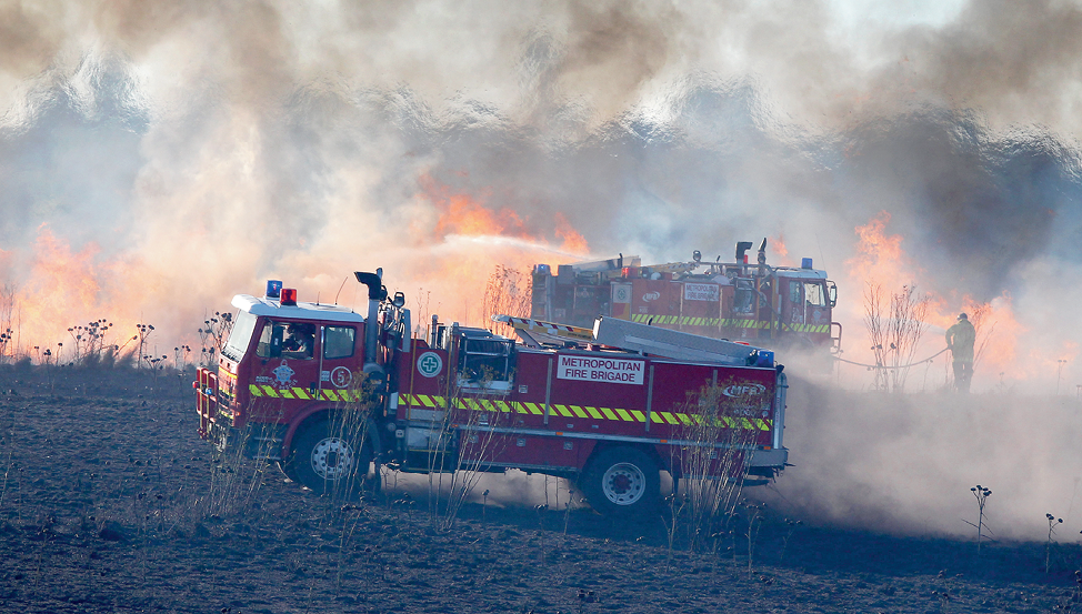 Photograph of emergency services vehicles and staff managing a grass fire