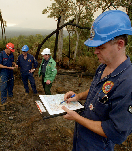 Photograph of an emergency services member looking at a map, with other members in the background