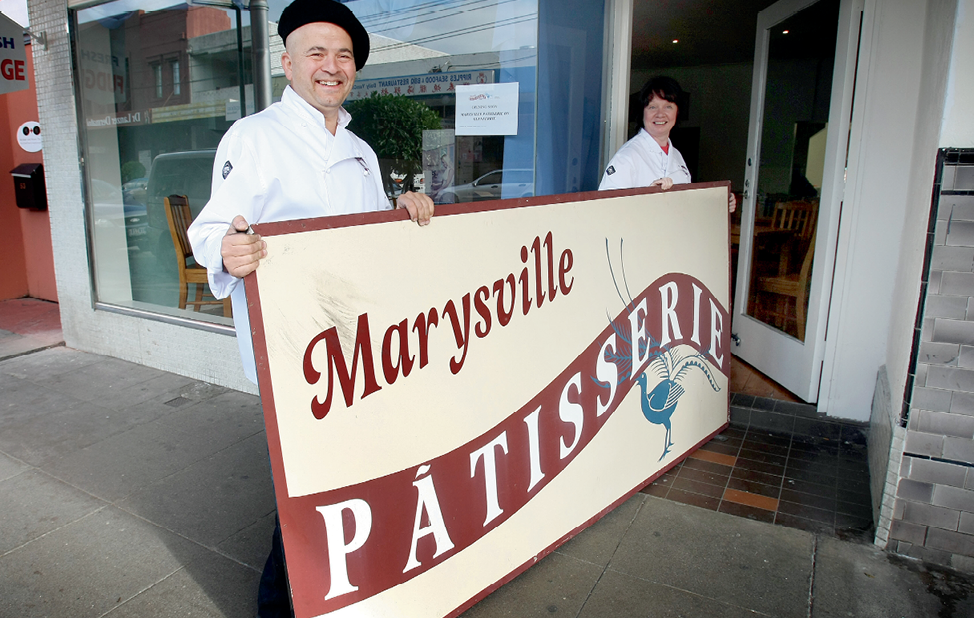 Photograph of Marysville Patisserie owners carrying the shop's sign