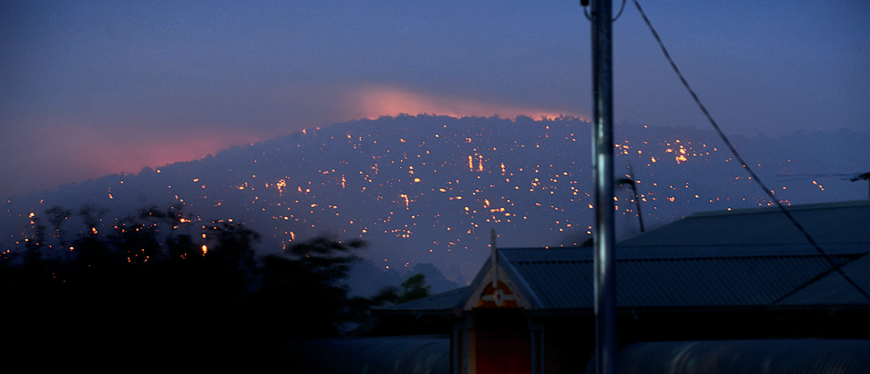 Photograph of a Perth hillside at night showing flames from fires