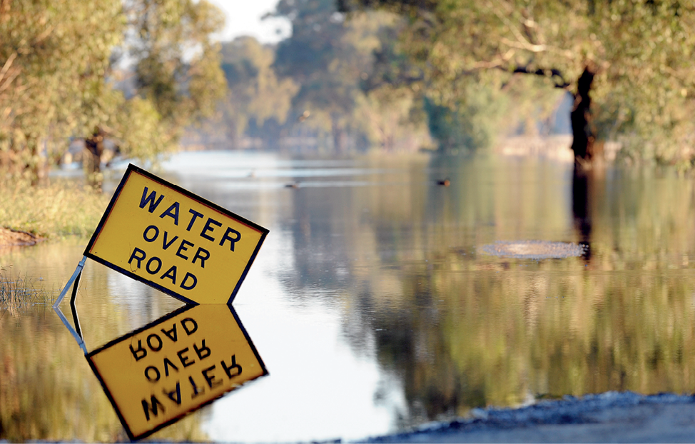 Photograph of a 'Water over road' hazard sign in floodwaters