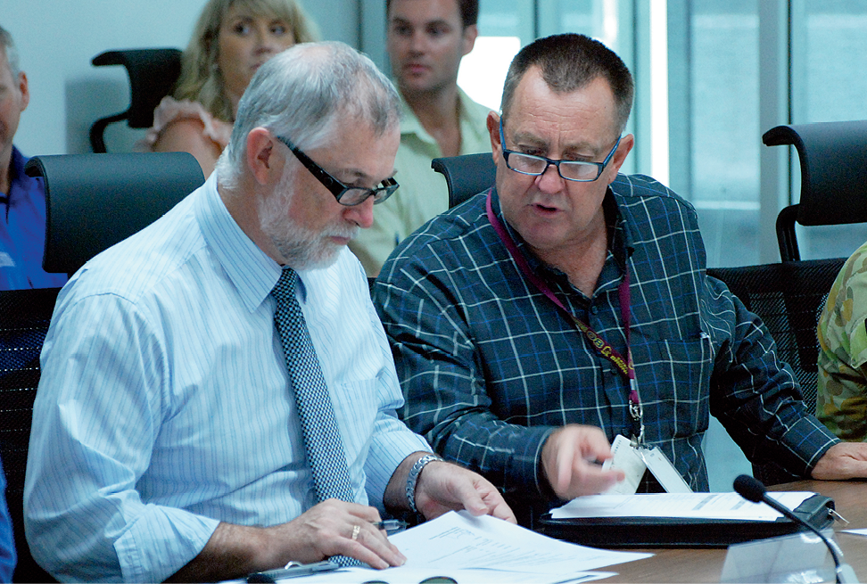 Photograph of Jim McGowan and Bruce Grady discussing meeting papers