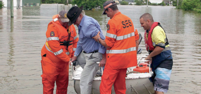 Photograph of SES workers in uniforms helping a man out of a small boat in floodwaters