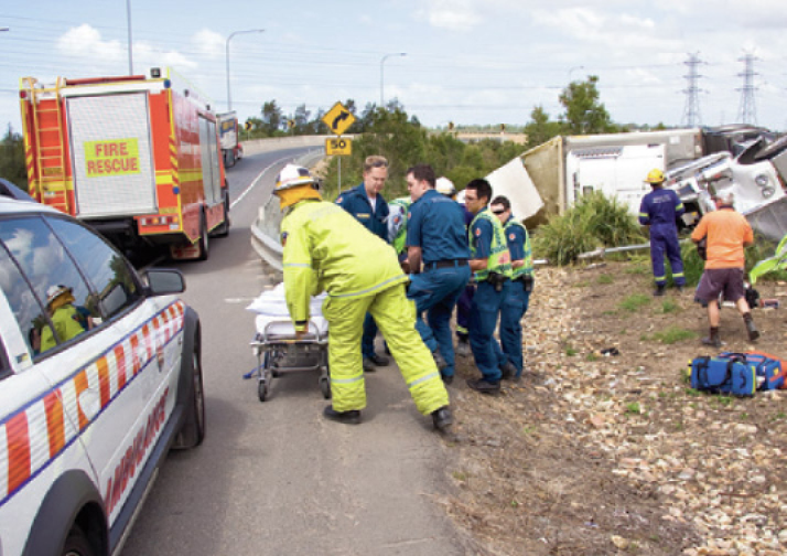 Photograph of emergency services staff in uniforms at the scene of a vehicle crash