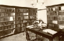 Photograph of a small library with bookshelves, a desk and a chair