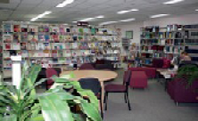 Photograph of a library with books, tables and chairs, and an indoor plant