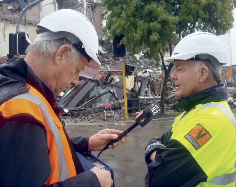 Photograph of John Hamilton being interviewed in a street with destroyed structures in the background