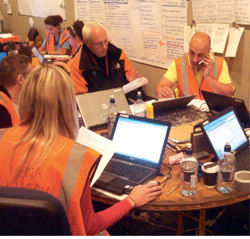 Photograph of team members in high-visibility clothing at a table with laptops and phones