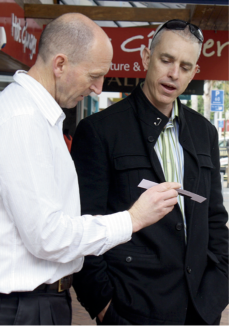 Photograph of James Lowe and David Phizacklea looking at a written scenario and talking