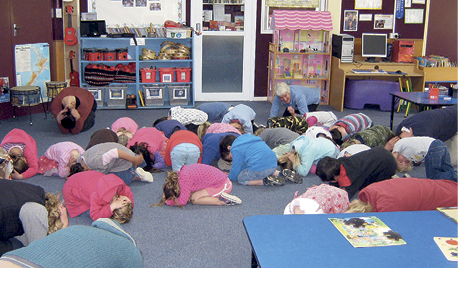 Photograph of kindergarten children crouching with heads down during the drill