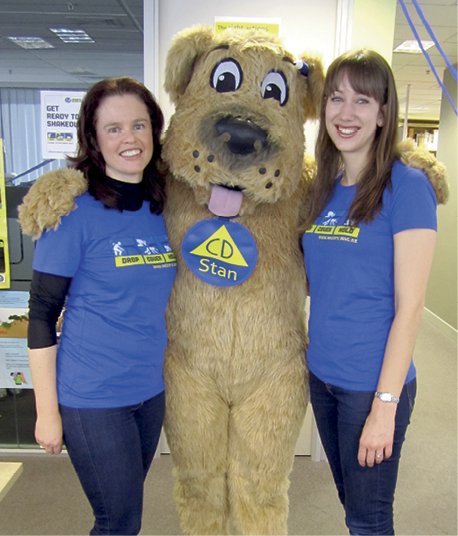 Photograph of Jo Guard and Anita Komen with a person in a 'Stan the Dog' suit
