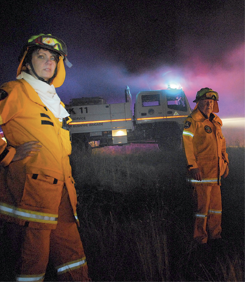 Photograph of a young woman and an older man in emergency services uniforms, with a fire truck and smoke in the background