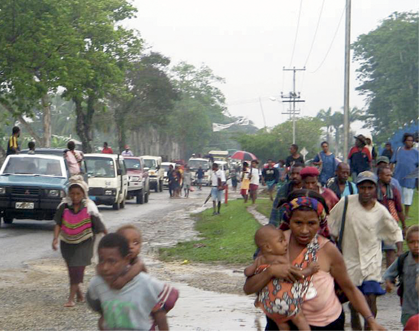 Photograph of cars on a road in the rain, with adults and children walking next to the road