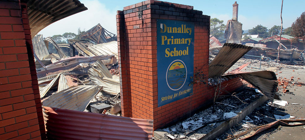 A brick entryway with the Dunalley Primary School sign surrounded by burnt-out ruins