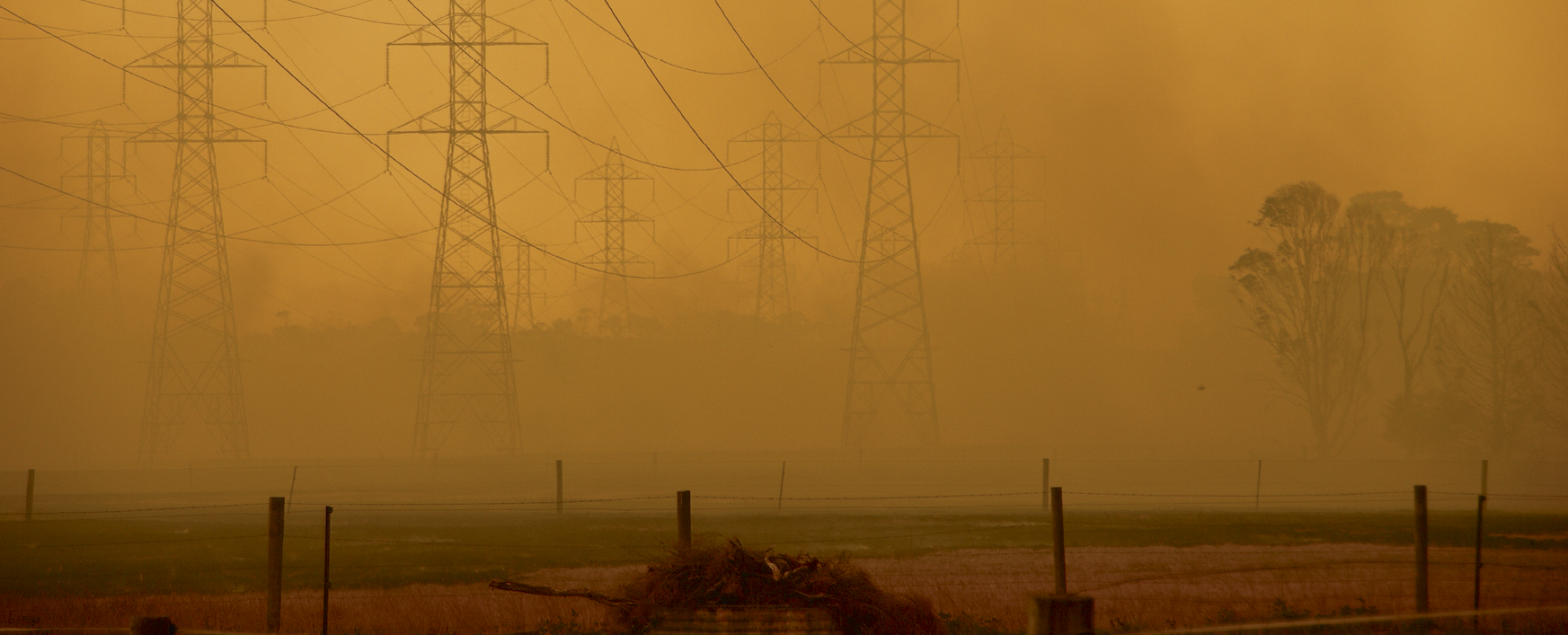 Electricity pylons in a rural setting shrouded in brown hazy bushfire smoke.