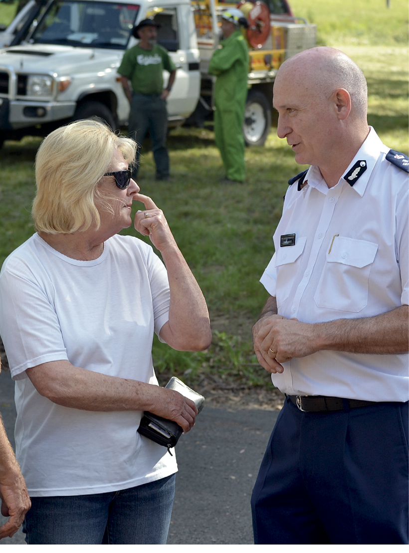 A male Fire Services Officer is talking with a middle-aged woman. In the background is a rural fire services vehicle and two men talking, one dressed in fire fighting clothing.