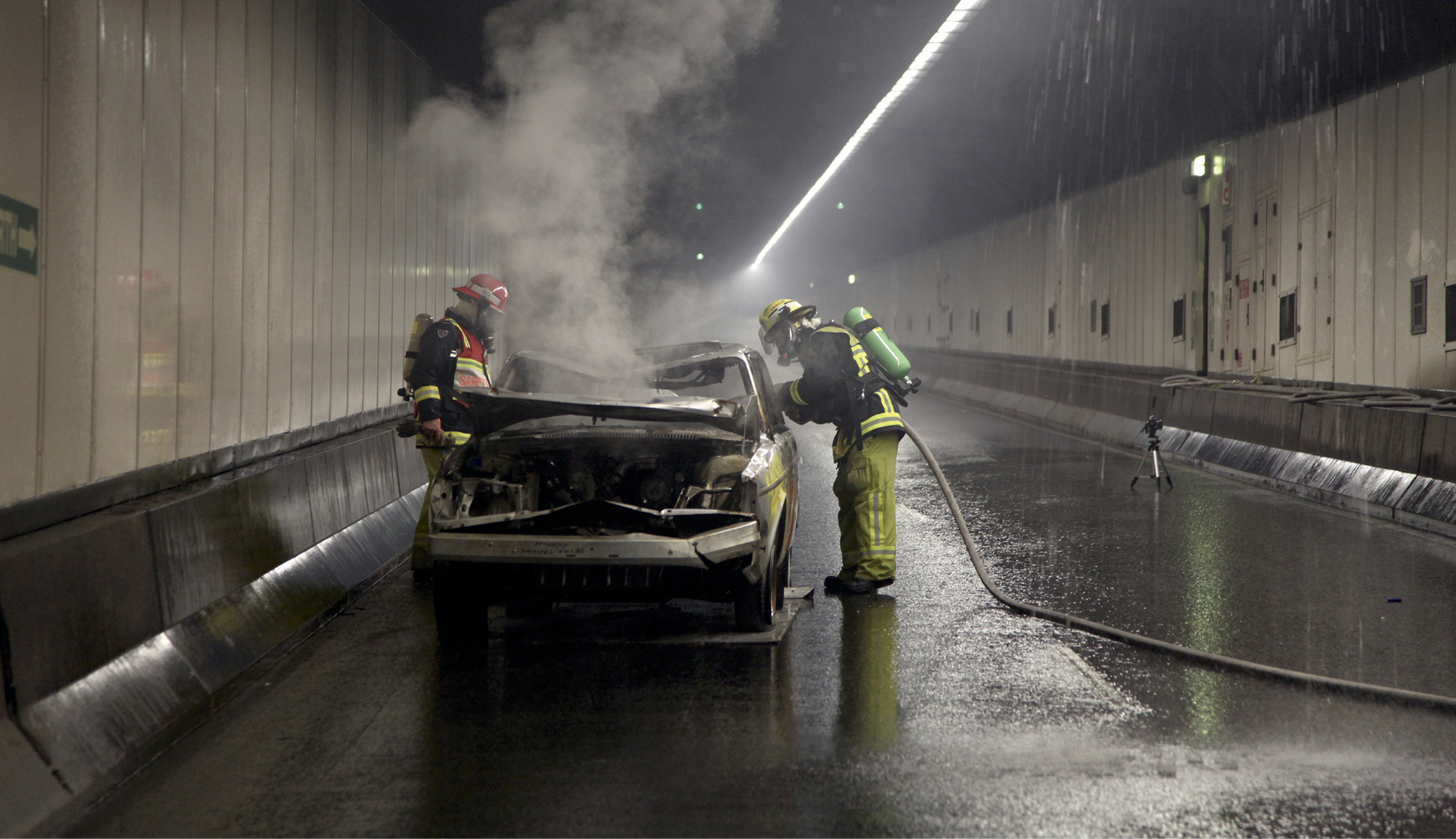 Two firefighters are hosing a burnt-out car inside a road tunnel. There is smoke rising from the bonnet of the car and water spraying from the roof of the tunnel.