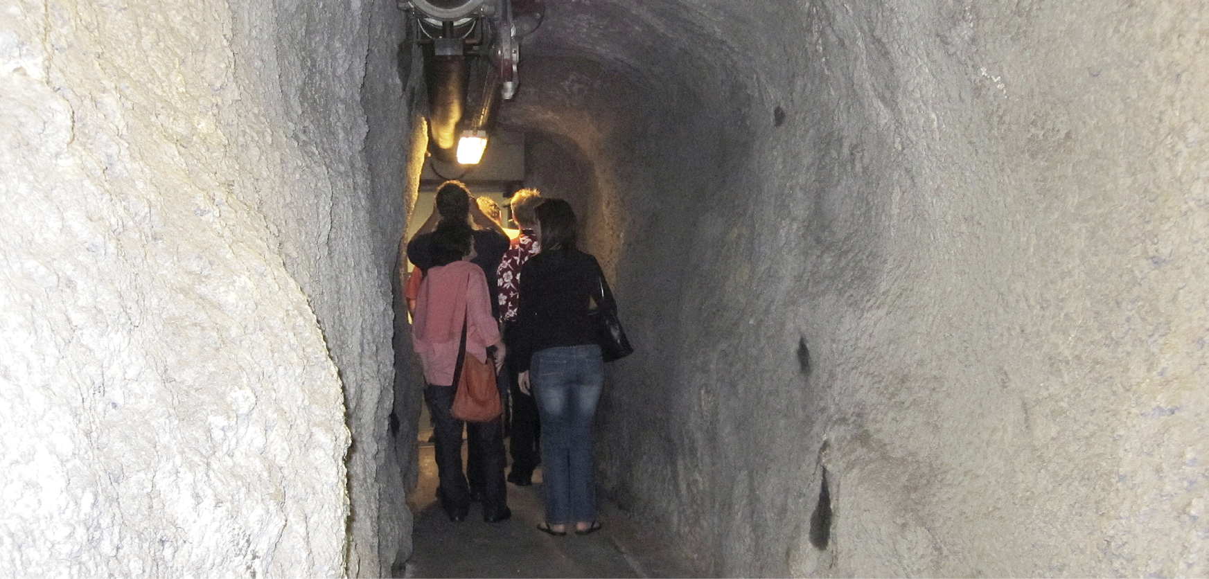 Photo of the inside of an exit cross-carriageway tunnel. The walls are roughly-hewn stone and there is a light overhead. Several adults are walking through the tunnel.