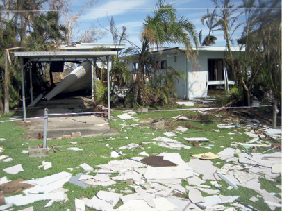 A single-storey house and carport has white sheets of asbestos debris covering the grassed yard.
