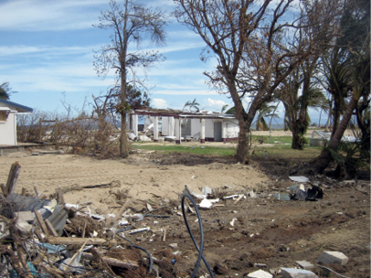 In the background are the standing remains of a partially destroyed single-storey house. In the foreground are piles of debris.