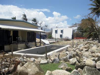 A single-storey house has a half-empty inground swimming pool surrounded by large rocks.