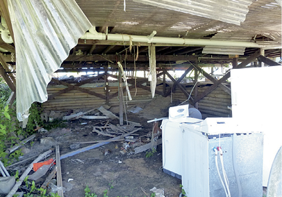 The interior of a large shed which is extensively damaged. There are some domestic washing machines and a fridge amongst the debris.