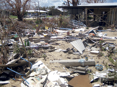 A yard is covered in debris including a variety of building materials. In the background is the standing remains of a single-storey house.