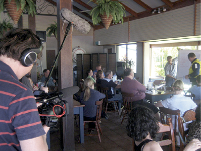 Many adults are seated in a vaulted dining room. They are facing a man in the background who is writing on a large flipchart. In the foreground is a man operating a television camera.