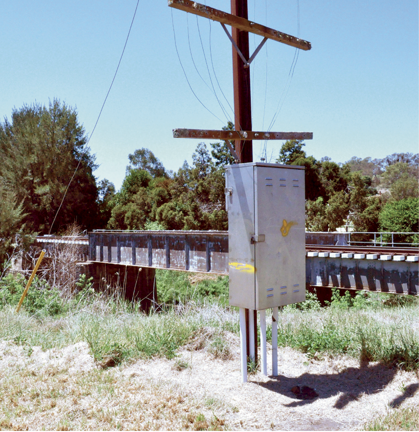An electrical box on a post has a yellow paint line one third of the way up the box, approximately level with the railway bridge beside it.