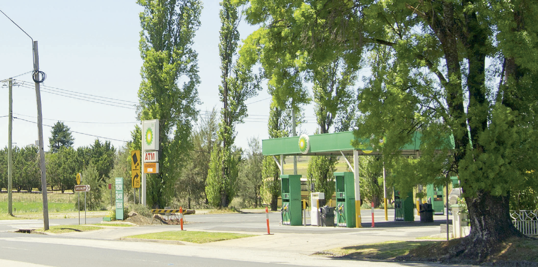 A BP petrol station surrounded by grassed areas and tall trees.