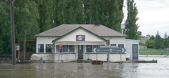 A cottage is surrounded by floodwaters.