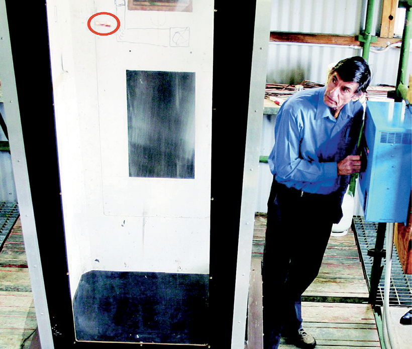 A man is turning a dial on a control box while observing a vertical wind tunnel.