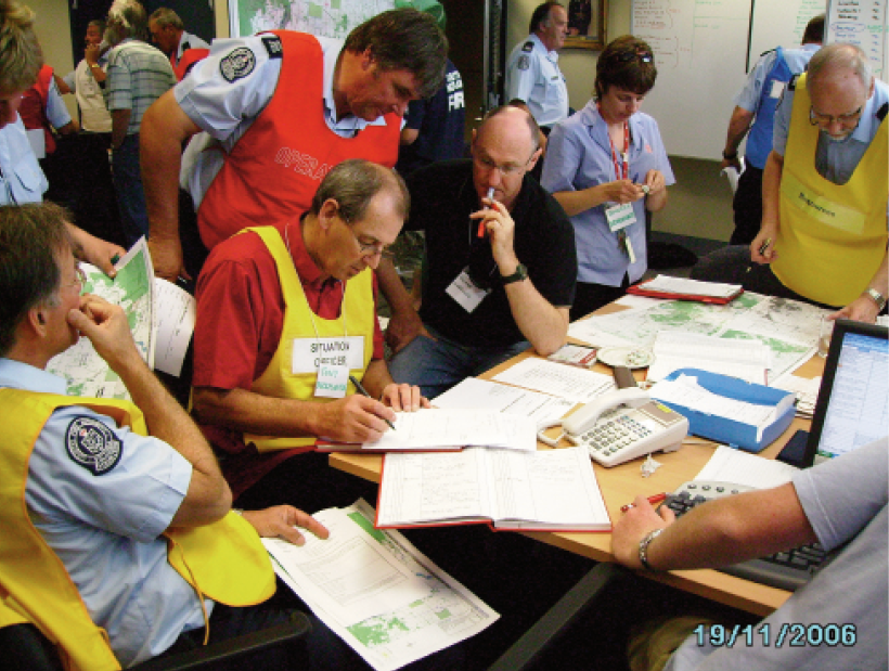 Several male and female emergency services personnel are gathered around a table covered in papers and maps