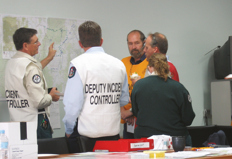 Five emergency services personnel are gathered around a wall map.