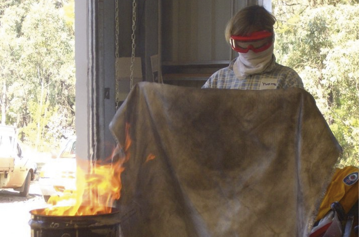 A woman wearing a protective face wrap and goggles is about to put out a small fire in a metal drum using a large cloth