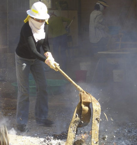 A woman wearing jeans, long-sleeve shirt, protective gloves, face-wrap, hard hat and glasses is putting out a small fire using a leather strap on a long handle.