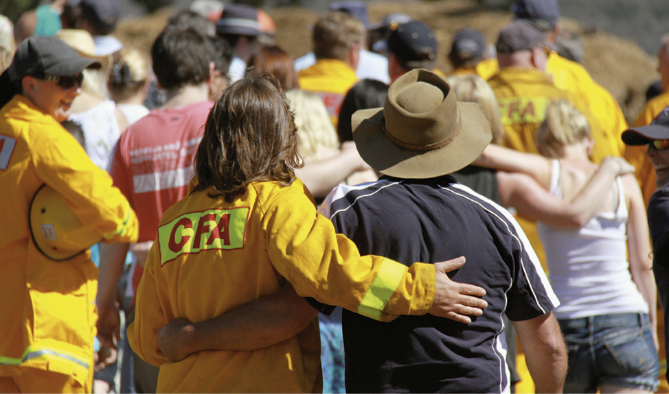 A group of men and women are walking away from the camera, some are dressed in CFA yellow uniforms, some have their arms around each other.