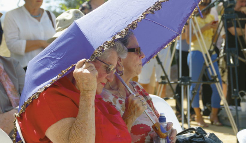 Two elderly women are shading themselves with an unbrella. There are more people standing in the background.